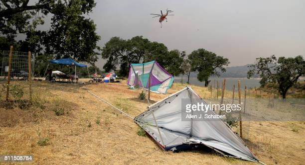 A firefigging helicopter passes by as tents food and personal belongs remain abandoned after campers were evacuated from the fastmoving Whittier Fire...