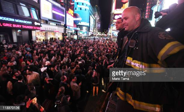 FDNY firefighter Aaron Clark looks on from atop a firetruck as people celebrate in Times Square after the death of accused 911 mastermind Osama bin...