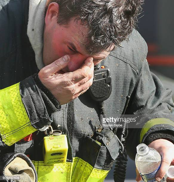 Firefighter Aaron LaBrecque with Ladder 21 rinses out his eyes as firefighters battle a multialarm fire at 238 Havre St in East Boston on Feb 27 2018...