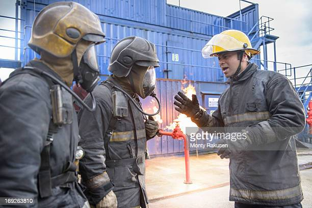 Firefighter advising trainees in respirators at fire simulation training facility