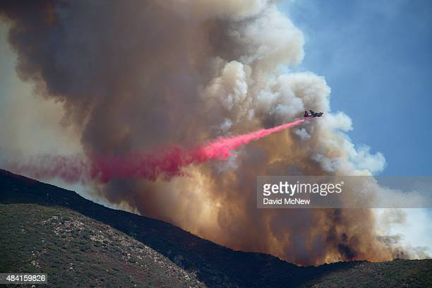 A firefighter aircraft drops fire retardant at the Cabin Fire in the Angeles National Forest on August 15 2015 north of Azusa California The fire has...