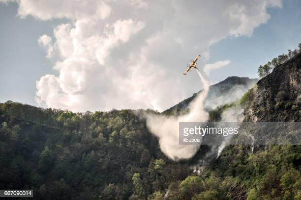 Firefighter airplane putting out a fire on mountain forest