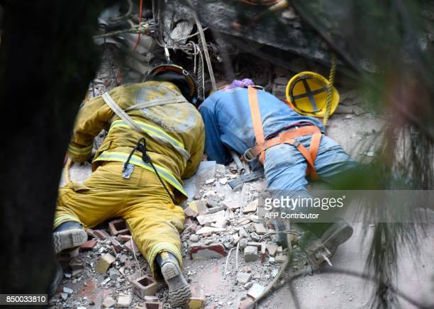 A firefighter and a rescuer search for survivors in Mexico City on September 20 2017 after a strong quake hit central Mexico on the eve A powerful 71...