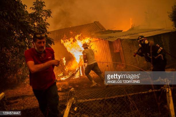 Firefighter and locals rush to a burning house in an attempt to extinguish forest fires that are approaching the village of Pefki on Evia island,...