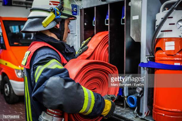Firefighter Arranging Hose In Rack At Fire Station