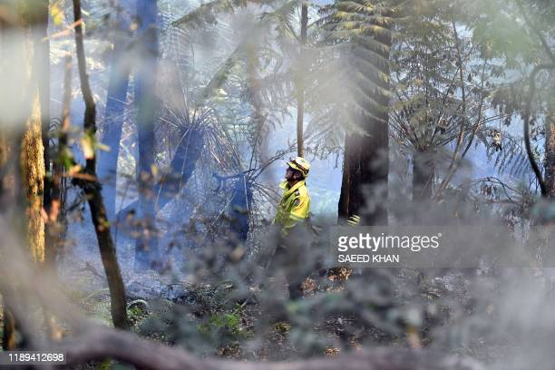 A firefighter attempts to extinguish a bushfire in Mount Weison in Blue Mountains some 120 kilometres northwest of Sydney on December 18 2019...