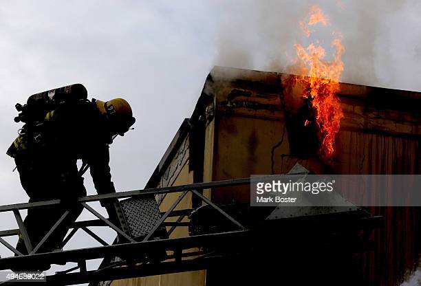 A firefighter backs down his ladder while the remains of stubborn fire flare through a ventillation hole in a retail bargain store on the 5700 block...
