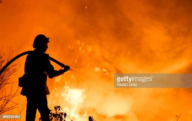 TOPSHOT A firefighter battles a wildfire as it burns along a hillside near homes in Santa Paula California on December 5 2017 Fastmoving windfueled...