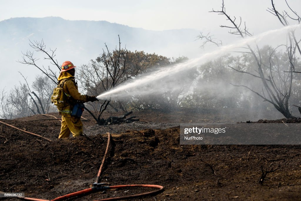Firefighter battles a wildfire in Mandeville Canyon in Los Angeles, California on May 28, 2017. More than 150 firefighters battle the fire that burns near multi-million dollar homes in the Brentwood neighborhood.