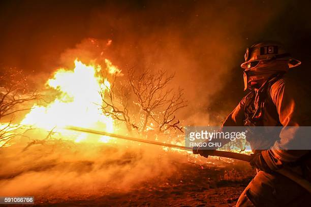 A firefighter battles the Blue Cut wildfire burning near Cajon Pass north of San Bernardino California on August 16 2016 A rapidly spreading fire...