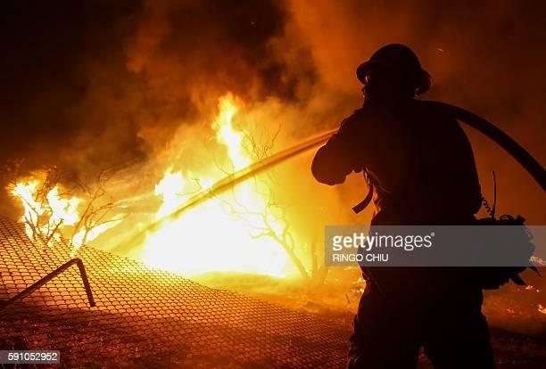 A firefighter battles the Blue Cut wildfire near Cajon Pass north of San Bernardino California on August 16 2016 A rapidly spreading fire raging east...