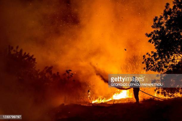 Firefighter battles the flame in a forest on the slopes of the Troodos mountain chain, as a giant fire rages on the Mediterranean island of Cyprus,...