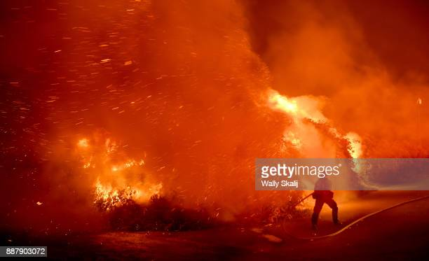 A firefighter battles the Thomas Fire in the town of La Conchita early Thursday morning