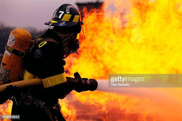 firefighter battling flame - fire protection suit stock photos and pictures