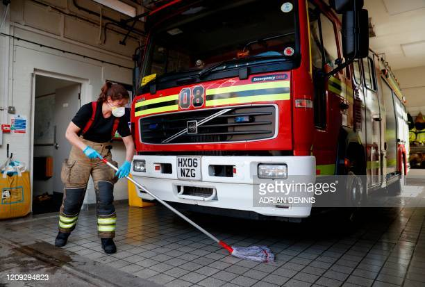 Firefighter Becky Wallis mops the engine bay after cleaning the fire engine at Station 08 following a call to a put out a wildfire in Hartley Wintney...