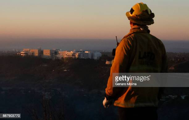 Firefighter Bobby D'Amico looks out over the Getty Center while monitoring the scene over BelAir where the Skirball fire has destroyed homes on...