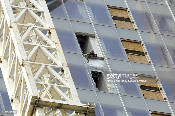 A firefighter breaks out the rest of a window that was damaged after a construction bucket fell 52 stories from future Bank of America building at...