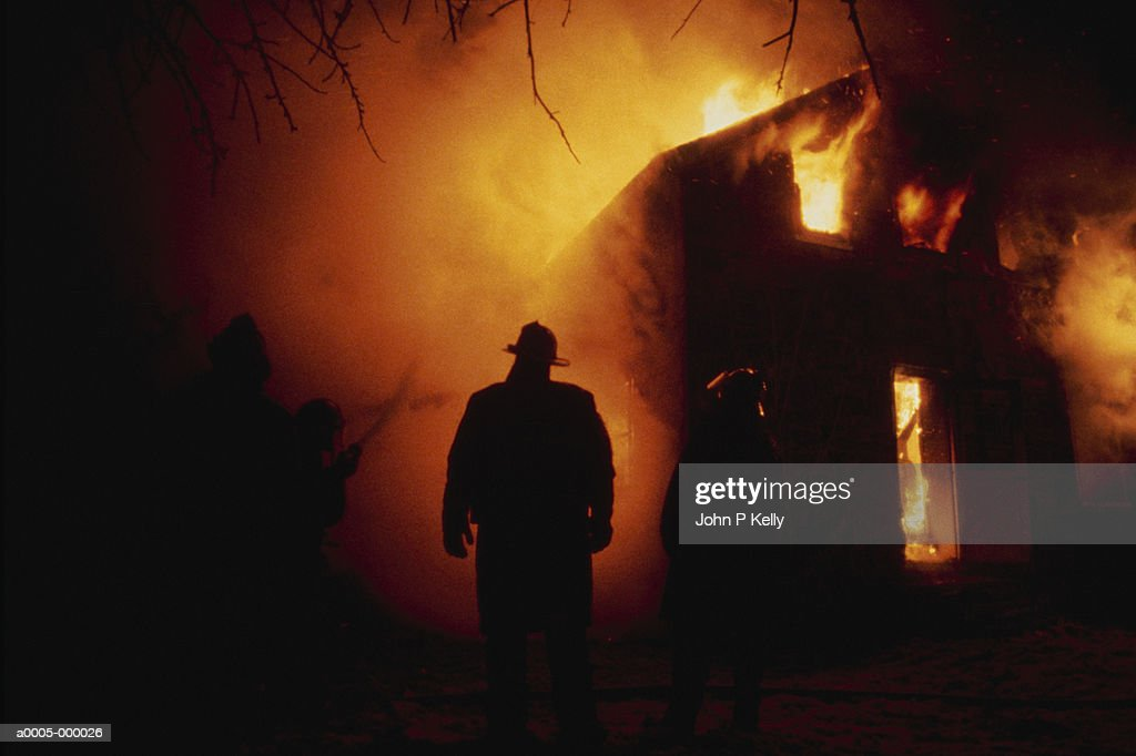 Firefighter By Flaming House : Stock Photo