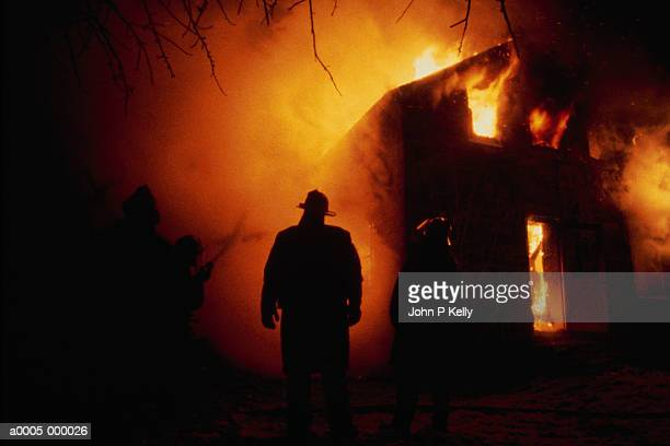 firefighter by flaming house - fire protection suit stock pictures, royalty-free photos & images