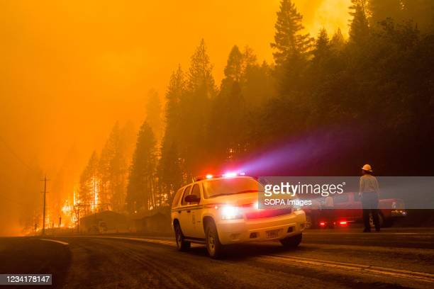 Firefighter car turn around as active flames reach highway 70. The Dixie fire continues to burn in California burning over 180,000 acres with 20%...