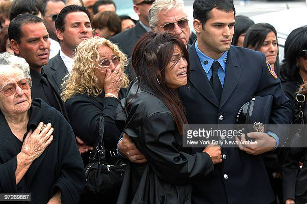 Firefighter Carmine Occhino comforts his mother, Ruth Ann, as his great-grandmother Nina Pizzi and grandmother, Mary Pizzi , grieve during funeral...