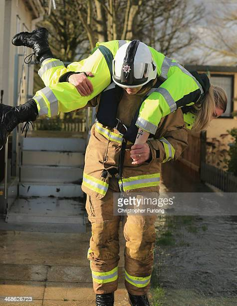 A firefighter carries a paramedic through floodwater on February 11 2014 in Chertsey United Kingdom The Environment Agency contiues to issue severe...