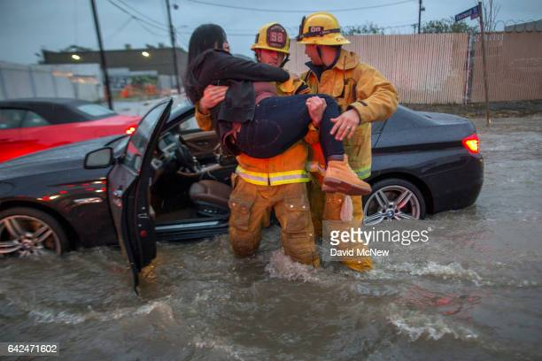 A firefighter carries a woman from her car after it was caught in street flooding as a powerful storm moves across Southern California on February 17...