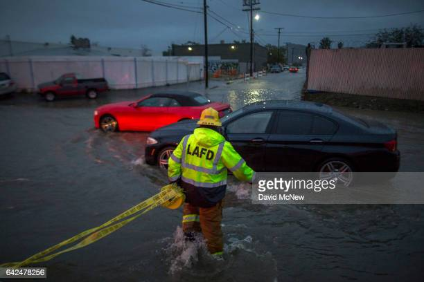 A firefighter carries caution tape in a flooded street as a powerful storm moves across Southern California on February 17 2017 in Sun Valley...