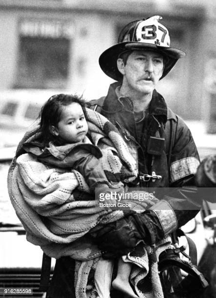 A firefighter carries one of several children rescued from a fire on Bancroft Street in the Jamaica Plain neighborhood of Boston to an ambulance on...