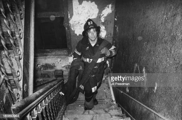 A firefighter carries the fire hose nozzle upstairs in an apartment block in the South Bronx New York City circa 1976