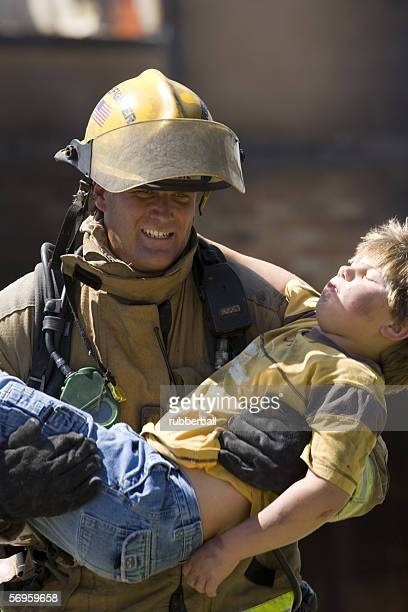 Firefighter carrying a wounded boy