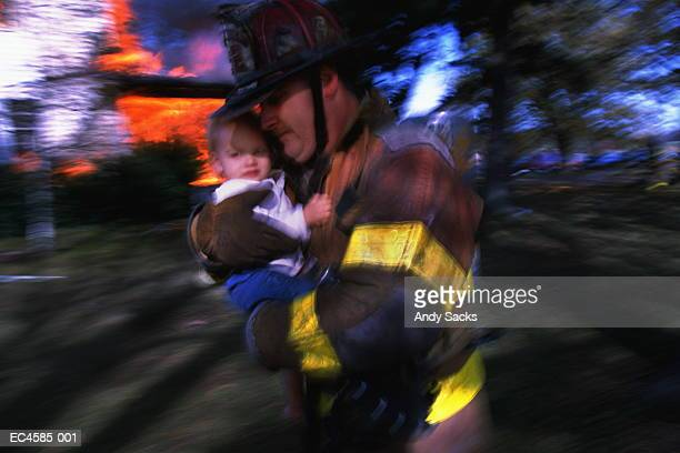 Firefighter carrying baby, blazing home in background (blurred motion)