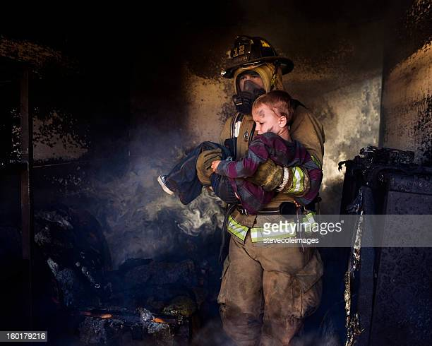 firefighter carrying boy - rescue stock pictures, royalty-free photos & images