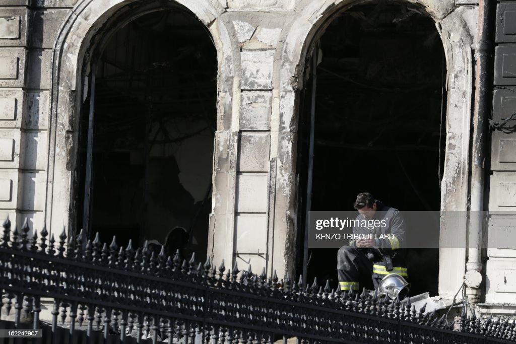 A firefighter checks his mobile phone on February 21, 2013 in the restaurant of the Paris nightclub L'Arc after a fire, believed to have been set by arsonists, swept through it in the early morning.