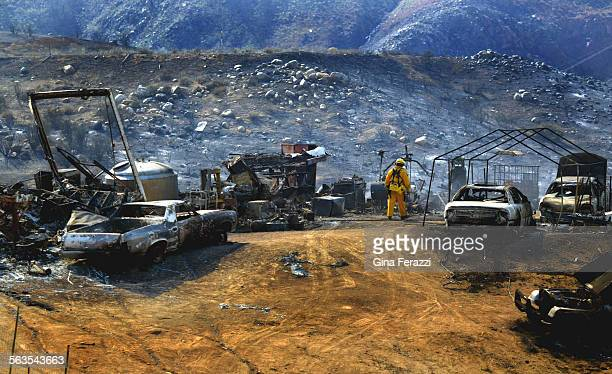 A CDF firefighter checks on smoldering cars and burned ruble destroyed by the El Cerrito fire Wednesday in the Temescal Canyon area north of Lake...