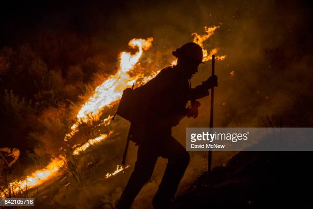 A firefighter climbs a burning hillside after having fallen into a hole fighting while the La Tuna Fire on September 2 2017 near Burbank California...