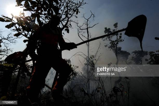 A firefighter combats a fire in the bush around Sobradinho 35 km from Brasilia on August 16 2010 Some 12000 fires are burning in Brazil on Monday...