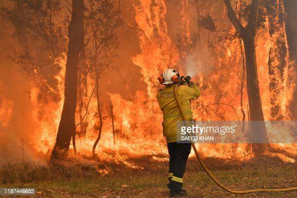 TOPSHOT A firefighter conducts backburning measures to secure residential areas from encroaching bushfires in the Central Coast some 90110 kilometres...
