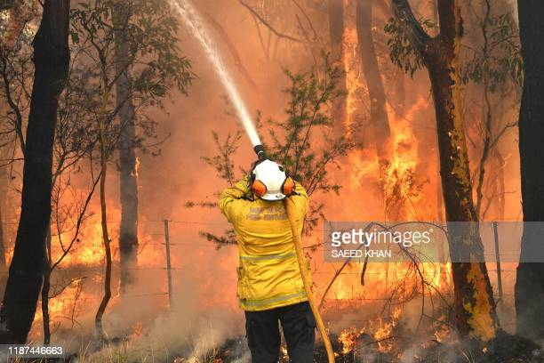 A firefighter conducts backburning measures to secure residential areas from encroaching bushfires in the Central Coast some 90110 kilometres north...
