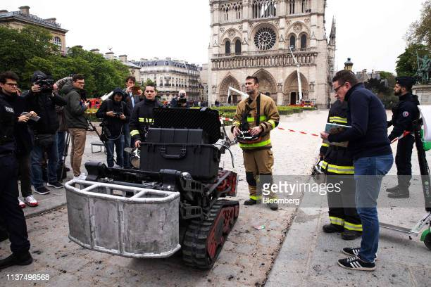 A firefighter controls a Colossus remote controlled intervention robot manufactured by Shark Robotics outside the firedamaged Notre Dame Cathedral in...