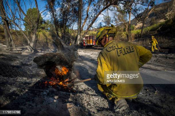 TOPSHOT A firefighter controls a hotspot of the Maria Fire in Santa Paula Ventura County California on November 02 2019