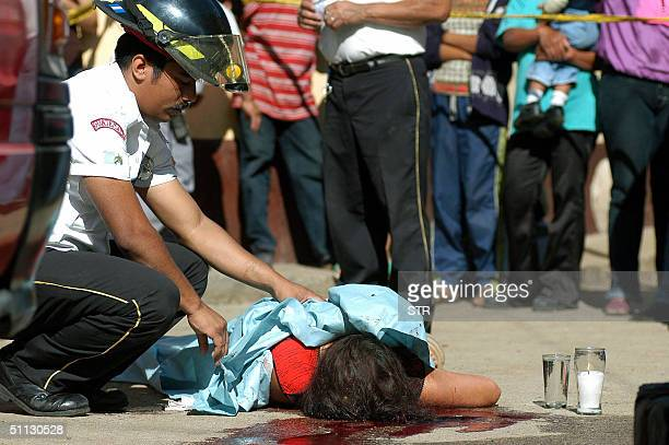 A firefighter covers the body of Flor De Maria Canel killed by two mareros in San Ignacio 20 km west of Guatemala City 30 July 2004 297 women have...