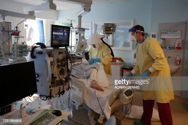 Firefighter Dan Joslin tends to a Covid-19 patient as he works alongside a critical care nurse in the Intensive Care Unit at Queen Alexandra Hospital...