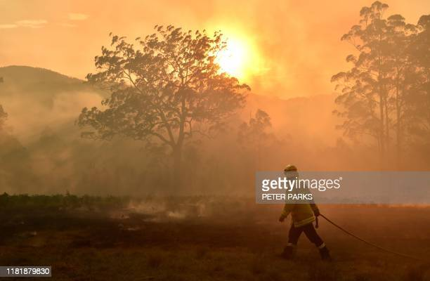 A firefighter defends a property from a bushfire at Hillville near Taree 350km north of Sydney on November 12 2019 A state of emergency was declared...