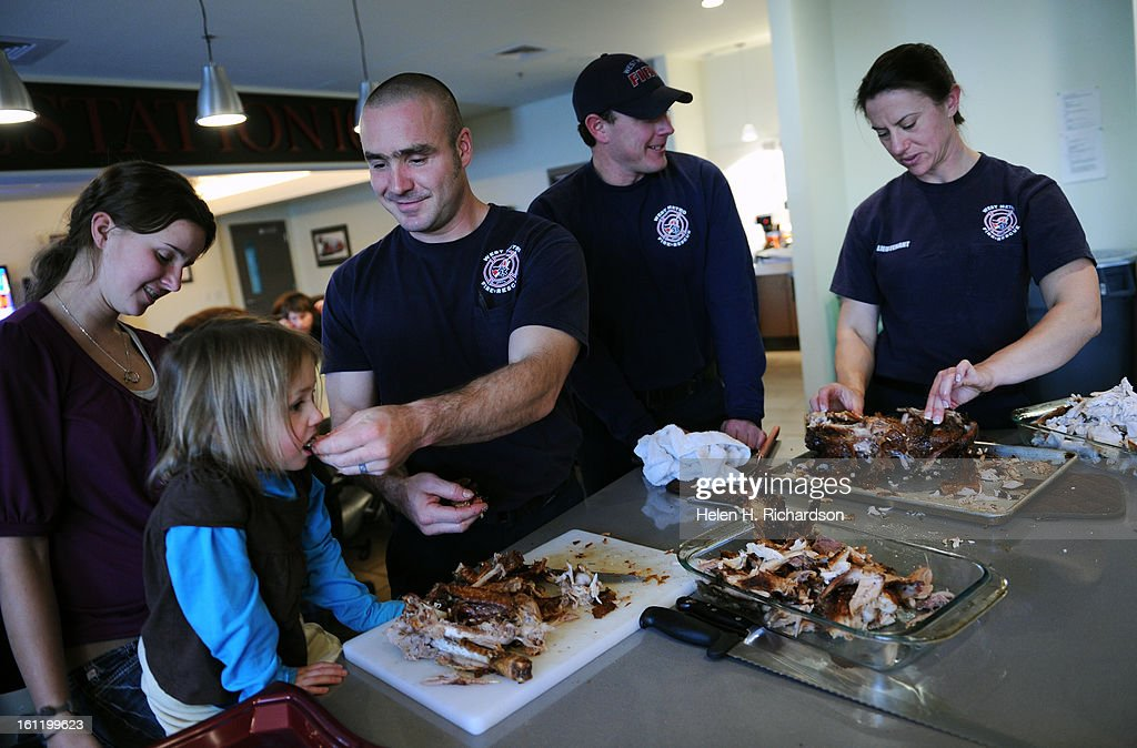 Firefighter Don Dority gives his daughter Mia, 3, a taste of the deep fried turkey. Family joined the crew for their Thanksgiving Day feast. At left is Amanda Williams, Dority's step daughter, And at right are Shane Erosky and Lt. Rachel Kohler who are carving up the turkey. West Metro fire station 10, located at 3535 South Kipling, enjoys a traditional Thanksgiving day meal in between calls. Today was like an average day with about 5 calls in 3 hours by 3:00 so far today. All their food was made by the crew on shift. 11 crew members are on the shift today at Station 10. Helen H. Richardson, The Denver Post