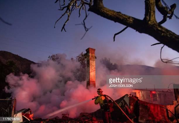 TOPSHOT A firefighter douses a smoldering home during the Hillside Fire in the North Park neighborhood of San Bernardino California on October 31...