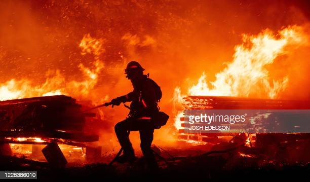 Firefighter douses flames as they push towards homes during the Creek fire in the Cascadel Woods area of unincorporated Madera County, California on...