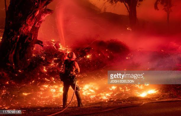 TOPSHOT A firefighter douses flames from a backfire during the Maria fire in Santa Paula California on November 1 2019