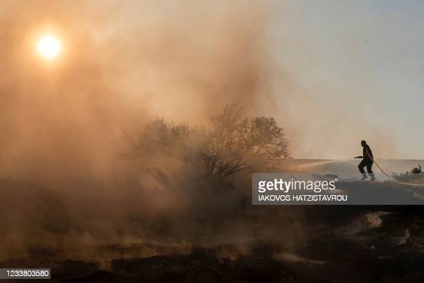 Firefighter douses the flames in an effort to contain a fire near the Kotsiatis area, on the outskirts of Cyprus' capital Nicosia on July 4, 2021. -...