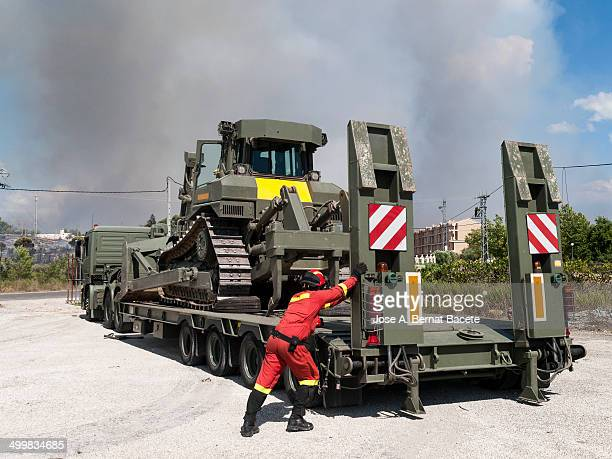 Firefighter downloading a large truck crawler dozer machine to build a fire in a forest fire. Emergency Military Unit. Bocairent,,Spain